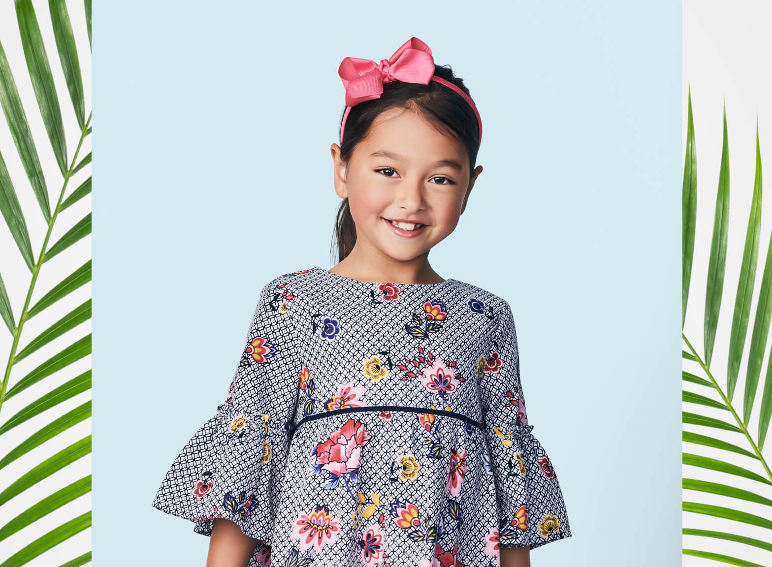 Young girl wearing floral dress and bow